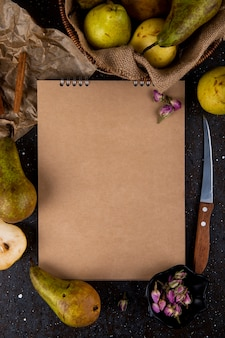 Top view of sketchbook with fresh ripe pears kitchen knife and cinnamon sticks on black background