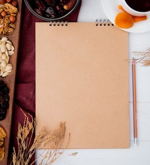 Top view of a sketchbook with mixed nuts and dried fruits on rustic