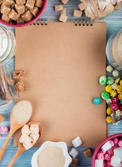 Top view of a sketchbook with various types of sugar and candies in bowls and glass jars arranged around on rustic background