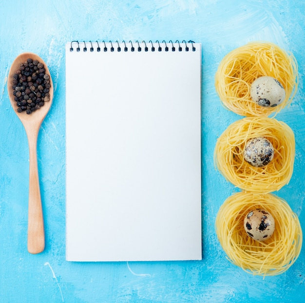 Top view of sketchbook yellow pasta nest with small quail eggs wooden spoon with pepper corns on blue background
