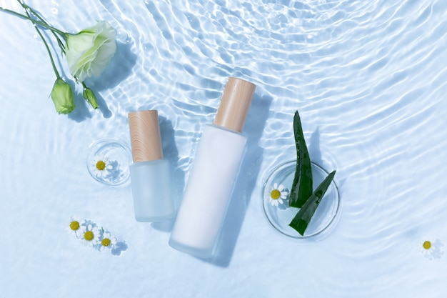 Top view of skincare bottles on a light blue water surface with aloe vera and daisy flowers