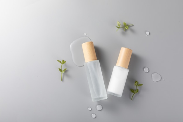 Top view of skincare bottles on a surface with green plants