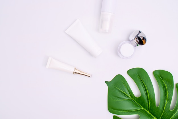 Top view, skincare and green leaves on a white table with copy space