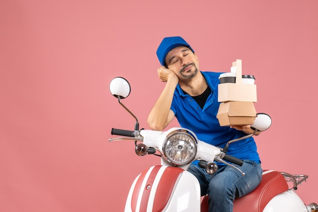 Vista dall'alto di un corriere assonnato che indossa un cappello seduto su uno scooter che mostra gli ordini su una pesca pastello