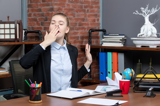 Top view of sleepy young female sitting at a table and holding the document yawning in the office