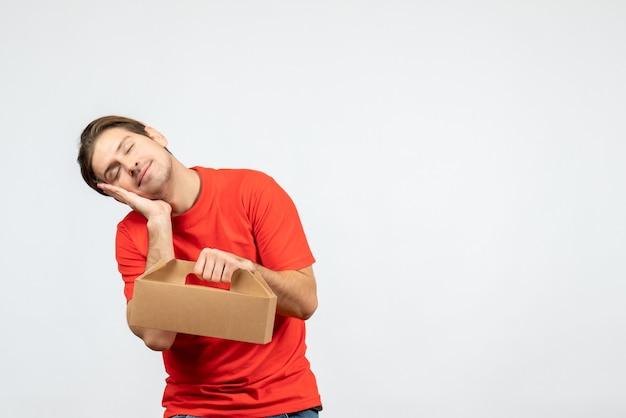 Vista dall'alto del giovane sonnolento in camicetta rossa che tiene scatola su sfondo bianco