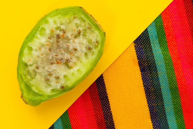 Top view slice of cactus fruit on yellow background