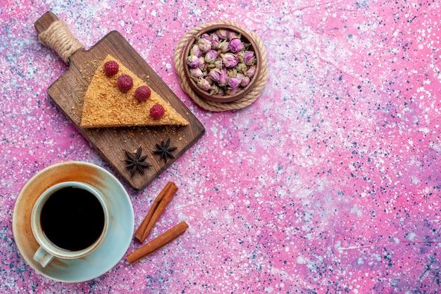 Vista dall'alto fetta di torta al forno e dolce con lamponi insieme a tè sulla scrivania rosa brillante cuocere torta dolce torta di frutta