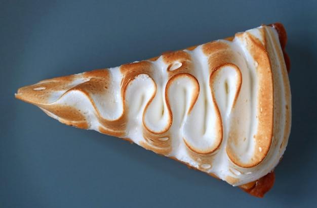 Top view of a slice of lemon meringue tart on blue plate