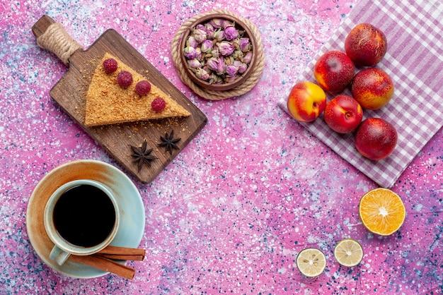 明るいピンクの机の上でお茶と桃と一緒にラズベリーと一緒に焼いて甘いケーキの上面図スライスは甘いケーキパイフルーツを焼きます