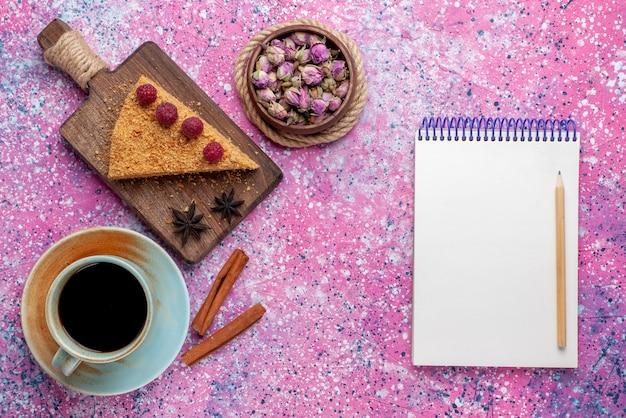 明るいピンクの机の上のお茶と一緒にラズベリーで焼いて甘いケーキの上面図スライスは甘いケーキパイフルーツを焼く