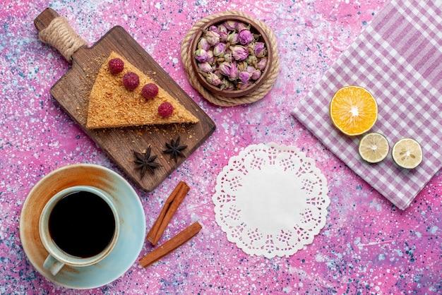 ピンクの机の上のお茶と一緒にラズベリーで焼いて甘いケーキの上面図スライスは甘いケーキパイフルーツを焼く
