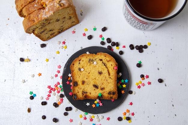 明るい背景のケーキ甘い砂糖ビスケットにカラフルなキャンディーと暗いプレート内のケーキのトップビュースライス