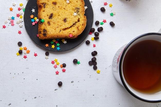 明るい背景に甘いカラフルなキャンディーと暗いプレート内のケーキの上面スライスケーキ甘い砂糖ビスケット焼き