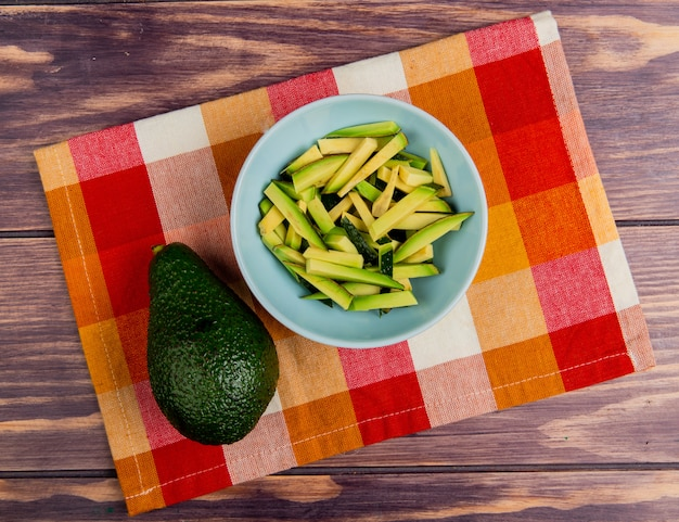 Top view of sliced avocado in bowl with whole one on cloth on wooden background