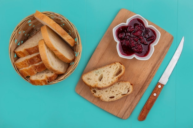 Top view of sliced baguette in basket and raspberry jam on cutting board with knife on blue background