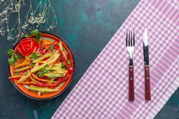 Vista dall'alto peperoni affettati insalata piccante colorata sulla scrivania blu scuro