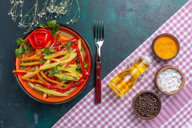 진한 파란색 책상에 조미료와 함께 얇게 썬 벨 후추 색의 매운 샐러드