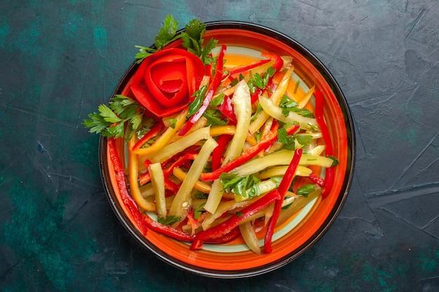 상위 뷰는 진한 파란색 배경에 접시 안에 피망 다른 색깔의 야채 샐러드를 슬라이스