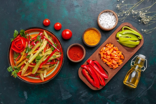 上面図スライスしたピーマン濃紺の背景に材料と油と異なる色の野菜サラダ