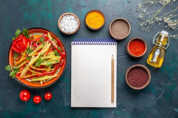 Vista dall'alto peperoni affettati insalata sana con diversi condimenti su sfondo blu scuro