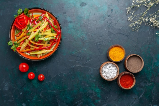 上面図スライスしたピーマンの健康的なサラダ、青の背景にさまざまな調味料