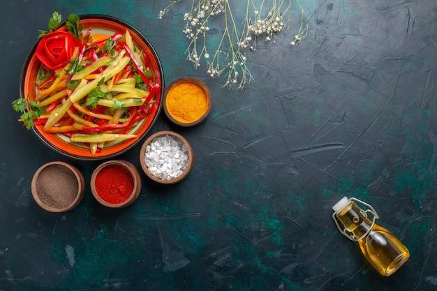 上面図スライスしたピーマンのオリーブオイルと濃紺の背景に調味料と健康的なサラダ