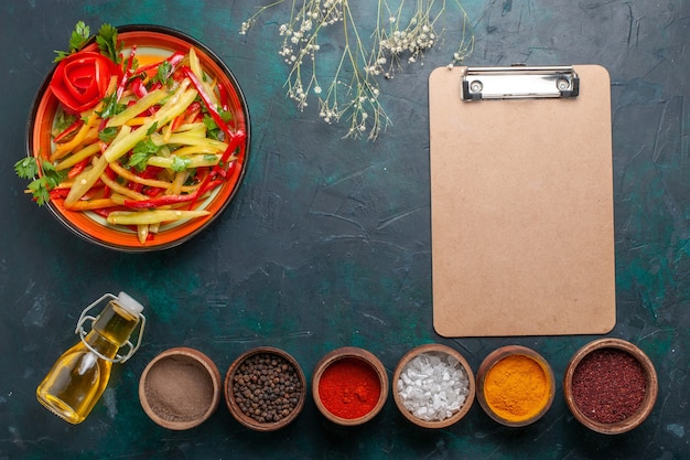 Vista dall'alto di peperoni affettati insalata sana con olio d'oliva e condimenti su sfondo blu scuro