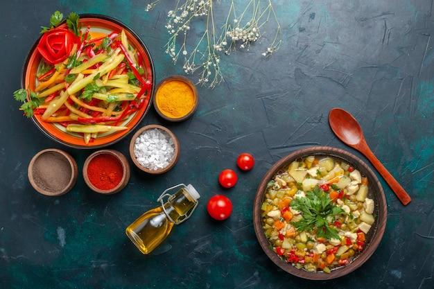 Insalata sana di peperoni affettati vista dall'alto con zuppa di olio d'oliva e condimenti sulla scrivania blu scuro