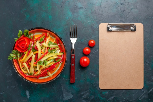 Vista dall'alto affettato insalata di peperoni all'interno della piastra con blocco note sulla scrivania scura