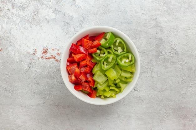 Vista dall'alto di peperoni affettati insalata piccante all'interno della piastra su sfondo bianco