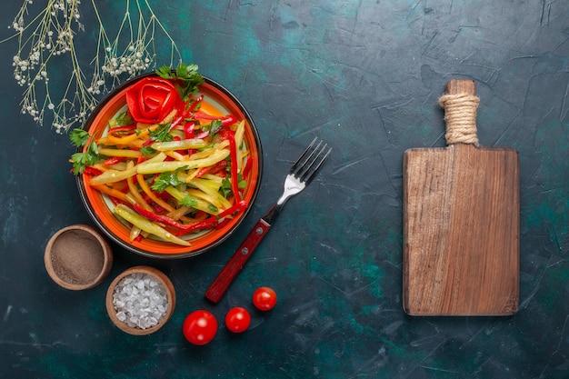 暗い背景に調味料とメモ帳でスライスしたピーマンのおいしい健康的なサラダの上面図