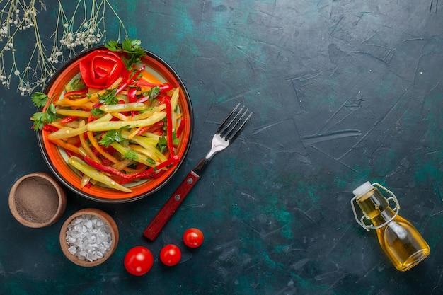 暗い床に調味料とオリーブオイルを添えた上から見たスライスしたピーマンのおいしいヘルシーサラダ