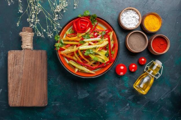 Vista dall'alto di peperoni affettati gustosa insalata sana con condimenti e olio d'oliva su sfondo scuro