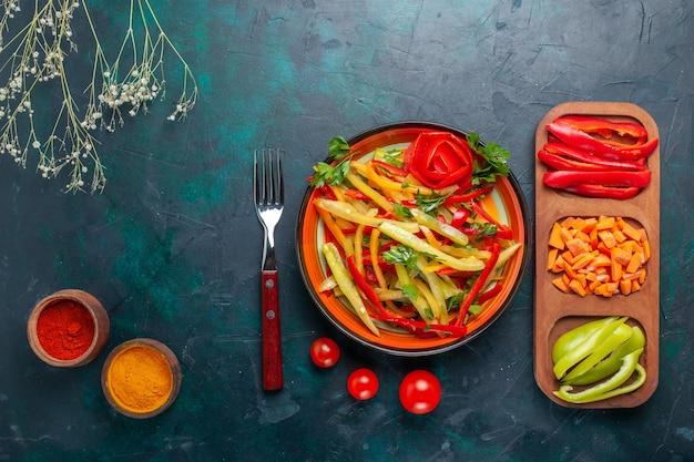 Vista dall'alto di peperoni affettati gustosa insalata sana con condimenti e altre verdure su sfondo scuro