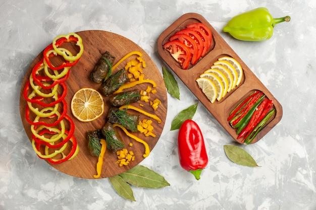 Vista dall'alto peperoni affettati con deliziosi dolma a foglia e verdure sulla scrivania bianca leggera