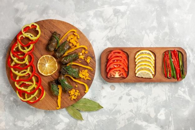 Vista dall'alto peperoni affettati con deliziosi dolma a foglia e verdure sulla scrivania bianca