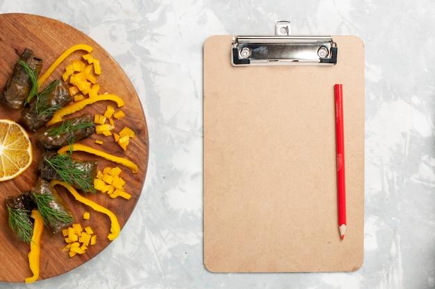 흰색 책상에 잎 돌마와 메모장 상위 뷰 슬라이스 벨 고추