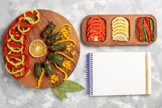 白い机の上に葉のドルマと野菜とスライスしたピーマンの上面図