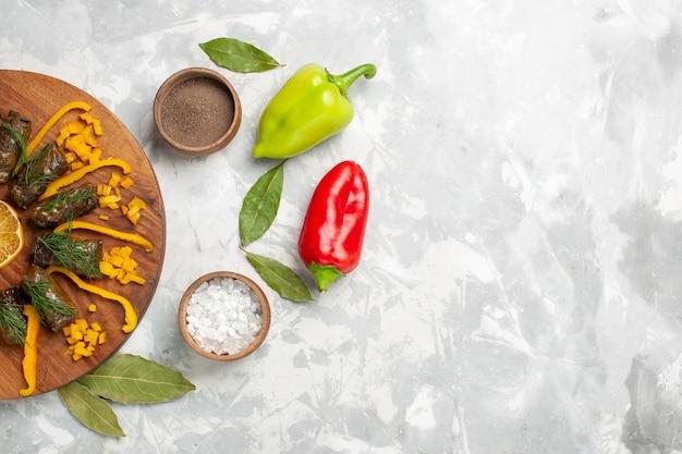 Vista dall'alto di peperoni affettati con dolma di foglia e verdure sulla scrivania bianca