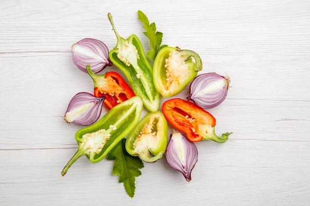 Peperoni affettati vista dall'alto con cipolle sul tavolo bianco