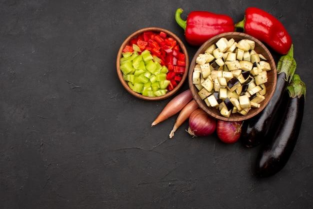 灰色の背景に赤いピーマンとナスのスライスしたピーマンの上面図スパイシーな温かい食事の食べ物