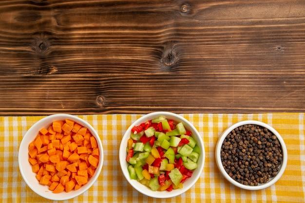 Vista dall'alto peperoni affettati con condimenti sull'insalata di salute cibo pasto vegetale tavolo in legno marrone