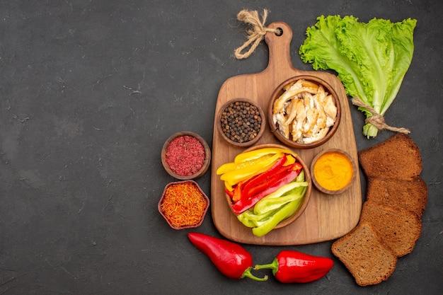 Vista dall'alto di peperoni a fette con condimenti e pane scuro su nero