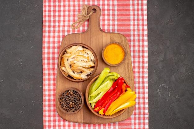 Vista dall'alto di peperoni a fette con condimenti e pane a fette su nero