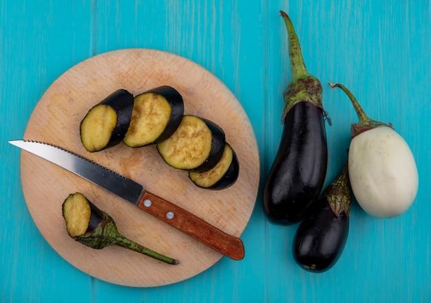 Vista dall'alto di melanzane nere a fette su un tagliere con un coltello e melanzane bianche su sfondo turchese