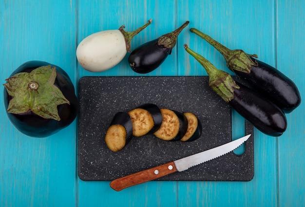 Vista dall'alto di melanzane nere a fette su un tagliere con un coltello e intero su uno sfondo turchese
