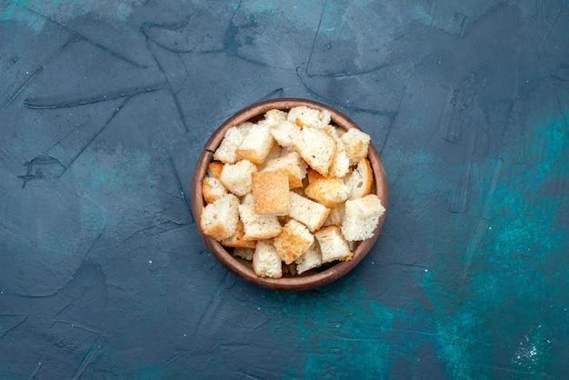 Вид сверху нарезанный хлеб в коричневой миске на темном столе, сухариках, закусках