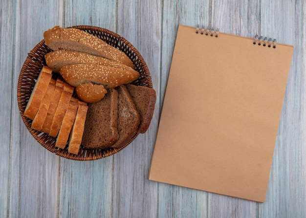 Top view of sliced breads as seeded brown cob crusty and rye ones in basket with note pad on wooden background with copy space