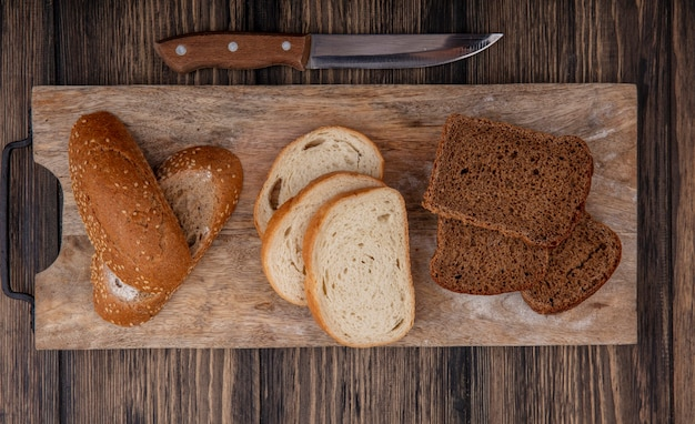 Top view of sliced breads as seeded brown cob white and rye ones on cutting board and knife on wooden background
